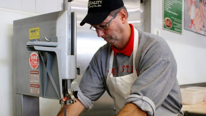 Ken Wassler cuts baby-back ribs at Wassler Meats in Bridgetown. He and his brother, Dave, are the fourth-generation owners of Wassler Meats.