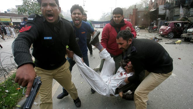Pakistani police officers and volunteers rush an injured man to a hospital after a bombing in Lahore, Pakistan, Tuesday, Feb. 17, 2015.