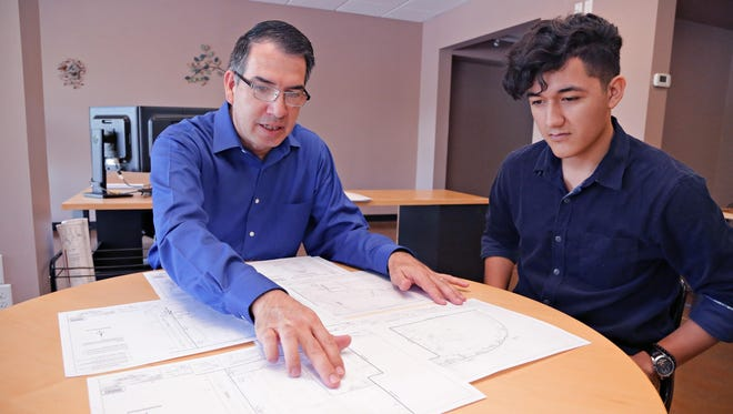 Patrick Ramirez (left), CEO of Assured Engineering Concepts, goes over a set of drawings rendered by Martin Flores, who will start ASU this fall to pursue a degree in architecture. He worked part time through high school at the south Phoenix engineering firm.
