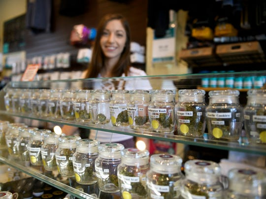 Trisha Stevens, a manager at Bloom City marijuana dispensary in Ann Arbor, works behind the counter on May 24, 2018.