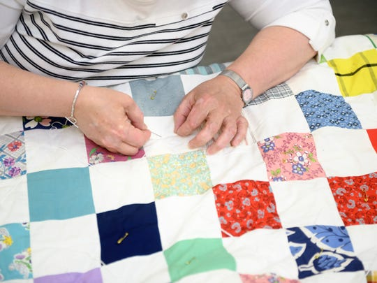 Member Jan Jacobs stitches a quilt during a recent meeting.