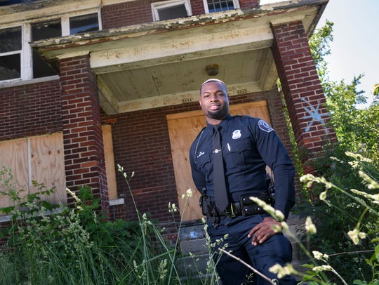 """""""I witnessed my first police raid across the street and that's when I knew I wanted to become a police officer,"""" said Detroit police officer Bryant George, standing in front of one of his childhood homes, now abandoned, in Detroit."""