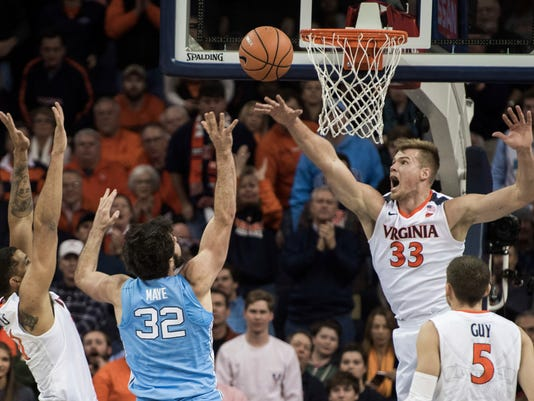 FILE - In this Jan. 6, 2018, file photo, Virginia's Jack Salt (33), Isaiah Wilkins, left, and Kyle Guy contest a shot by North Carolina's Luke Maye (32) during first half of an NCAA college basketball game in Charlottesville, Va. The Cavaliers lead the nation in scoring defense, allowing 52.7 points per game. (AP Photo/ Lee Luther Jr., File)