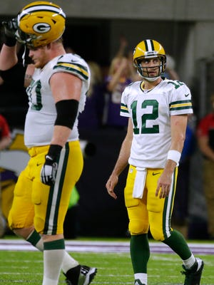 Green Bay Packers quarterback Aaron Rodgers walks off the field after throwing an interception.