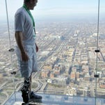 "Zac Vawter stands on ""The Ledge"" of the Willis Tower in Chicago after walking up the stairs of the building Sunday, Nov. 4, 2012, to become the first person to climb the 103 floors of one of the world's tallest skyscrapers with a bionic leg."