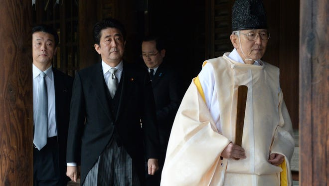 A Shinto priest leads Japanese Prime Minister Shinzo Abe as he visits the controversial Yasukuni war shrine in Tokyo.