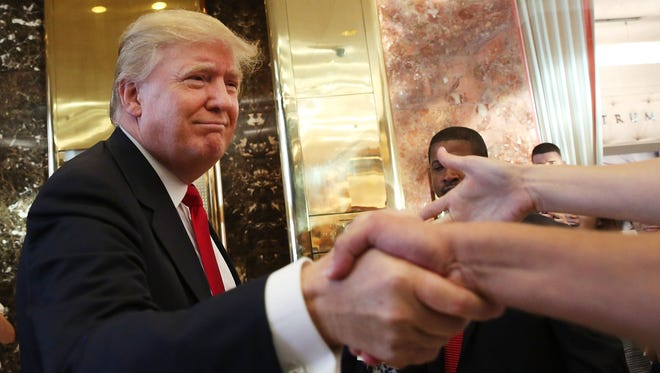 Donald Trump greets supporters and tourists after taping an interview with Anderson Cooper at a Trump-owned building in New York City on July 22, 2015.