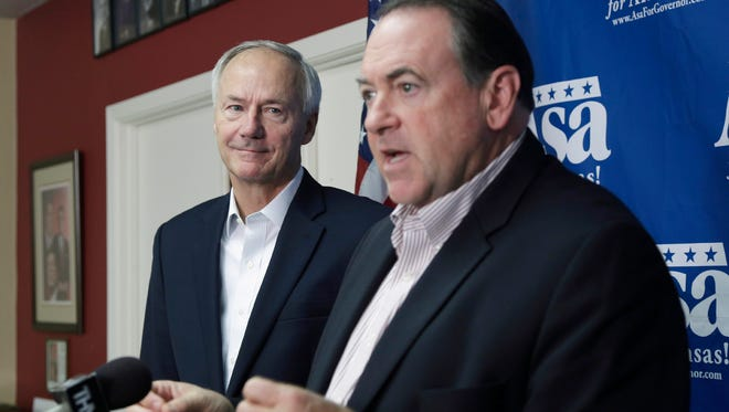 File - In this Oct. 9, 2014 file photo, Republican candidate for Arkansas governor Asa Hutchinson, left, listens as former Arkansas Gov. Mike Huckabee speaks during a news conference at Republican Party of Arkansas headquarters in Little Rock, Ark. Arkansas Gov. Hutchinson and several other top Arkansas Republicans who had backed Huckabee's presidential campaign said they're not ready to announce endorsements in the crowded race. Huckabee dropped out after a dismal showing in the Iowa caucuses