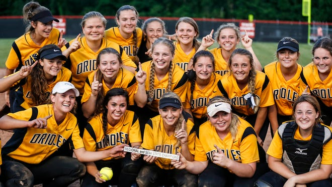 The Avon girls softball team posing with Semi-State Championship title and flashing their number one after beating Franklin Central 4-0 at Center Grove.