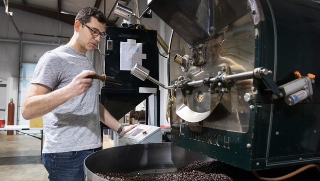 Craig King, lead roaster at West End Coffee, checks on coffee beans at the roastery on Tuesday, March 21, 2017.