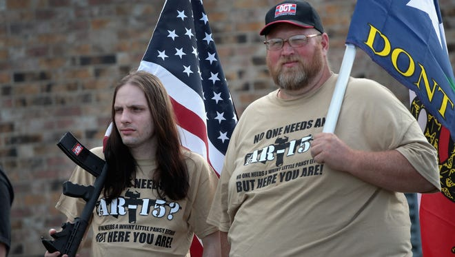"""Gun rights advocates stage a counter-protest near a March for Our Lives rally on March 24, 2018, in Killeen, Texas. These two wear T-shirts reading: """"No one needs an AR-15? No one needs a whiny little pansy either but her you are."""""""