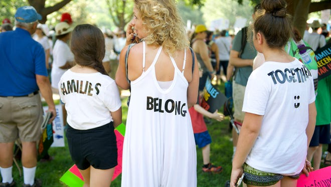 """Jess Emhoff and her daughters, Averi (left) and Eden (right), collectively wear the words """"Families Belong Together"""" on the backs of their clothes in Washington, DC."""