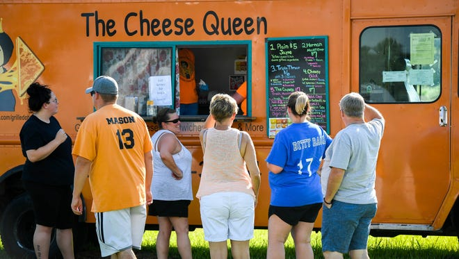 Diners lineup in front of The Cheese Queen food truck during the Food Trucks at the Farm event hosted by the Evansville Food Truck Association at Farm 57 every Wednesday, July 11, 2018.