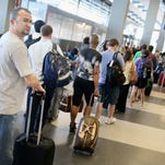 Passengers wait in line to check in for flights at O'Hare International Airport on May 23, 2014, in Chicago.