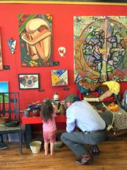 U.S. Sen. Tom Udall converses with a young artist while visiting Carrizozo to talk about arts-based economics.