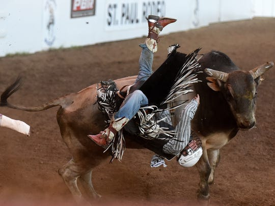 Cody Casper competes in bull riding at the St. Paul Rodeo on Tuesday, June 30, 2015.