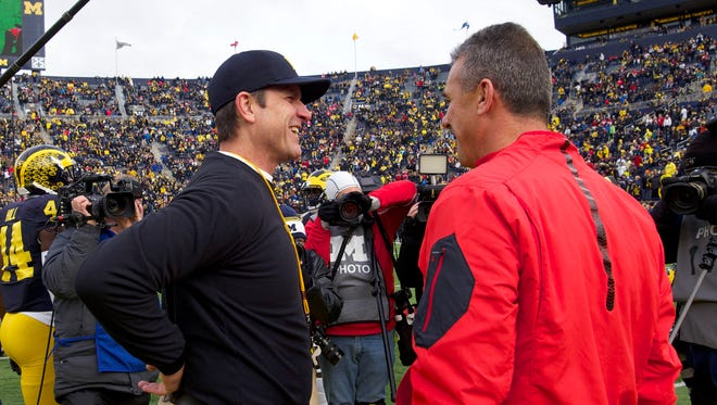Michigan coach Jim Harbaugh, left, greets Ohio State coach Urban Meyer before an NCAA college football game in Ann Arbor on Nov. 28, 2015.