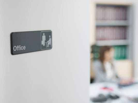 Office Sign with Worker in Background