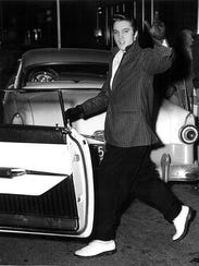 Elvis Presley had time for a smile and a wave as he left the Captain Shreve Hotel en route to a concert at Hirsch Coliseum.