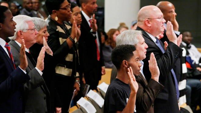 Rasheen Lamont Aldridge Jr. along with other members are sworn in by Missouri Gov. Jay Nixon at The Ferguson Commission swearing in in St. Louis on Nov. 18, 2014.