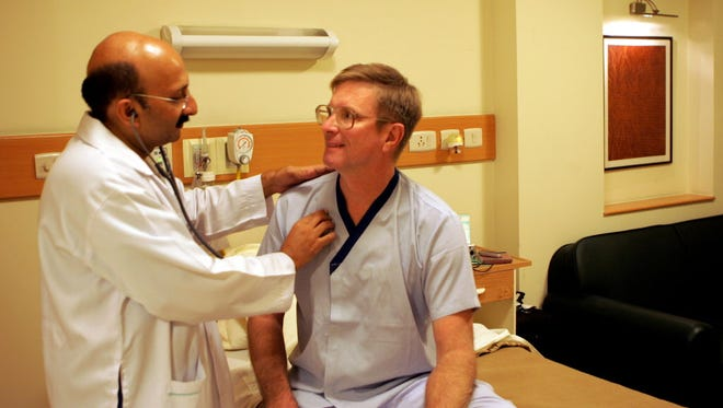 Doctor Praveen Chandra checks on an American patient after surgery in New Delhi, India, in 2006.