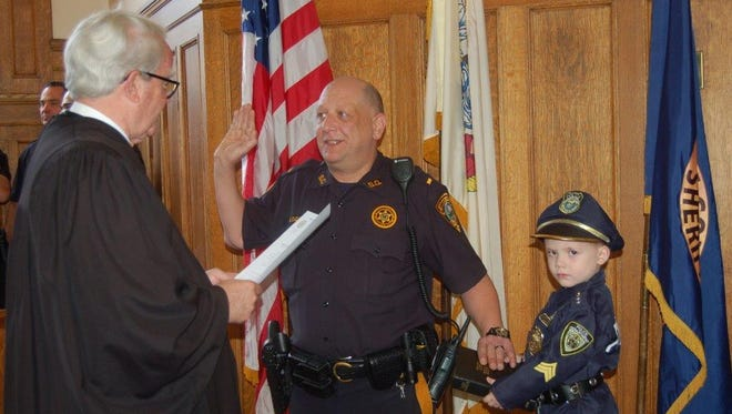 Lt. Michael DiGuilio is sworn in with the help of his 4-year-old grandson, Trenton Rhea, who also aspires to a career in law enforcement.