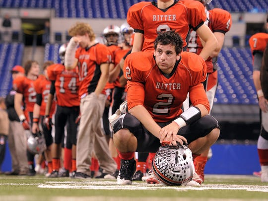 FILE – Cardinal Ritter's QB Jake Purichia kneels dejected with his teammate following their Class 2A High School football championship game at Lucas Oil Stadium.