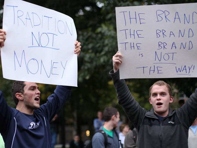 Ruben Rumbaut, left, a comparison from Beverly Hills, and Ryan Graham, right, a Senior from Grosse Pointe Park, reason signs and intone during a Fire Dave Brandon convene on Tuesday, Sept. 30, 2014 during a University of Michigan in Ann Arbor.