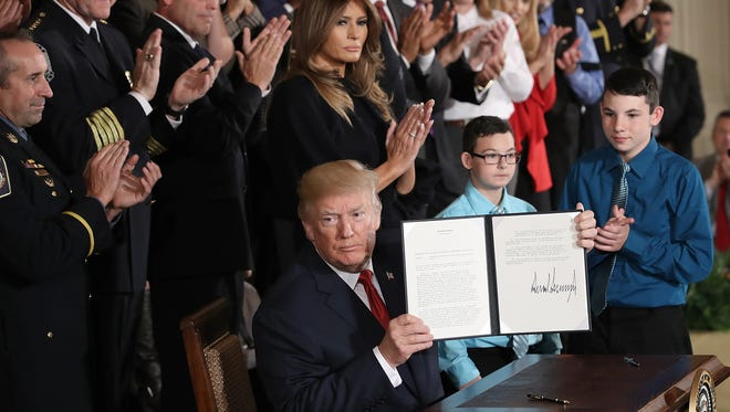 President Trump displays a signed presidential memorandum during an event highlighting efforts to battle the opioid crisis on Oct. 26, 2017.