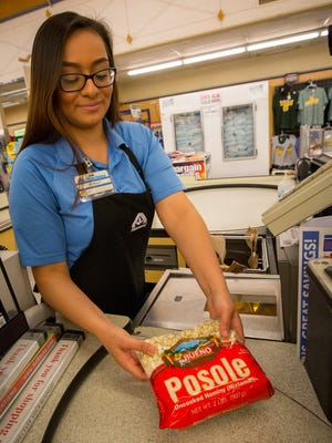 Cashier Shelly Ramos rings up a package of Bueno Foods posole at an Albertson's store, May 11, 2016.