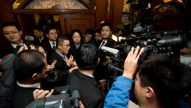 CEO of Malaysia Airlines Ignatius Ong, center, speaks to the media Monday outside a hotel room for relatives or friends of passengers aboard a missing Malaysia Airlines airplane in Beijing, China. Vietnamese aircraft spotted what they suspected was one of the doors of the missing Boeing 777 on Sunday, while questions emerged about how two passengers managed to board the ill-fated aircraft using stolen passports.