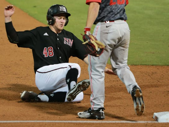New Mexico State's Cameron Haskins slides safely into
