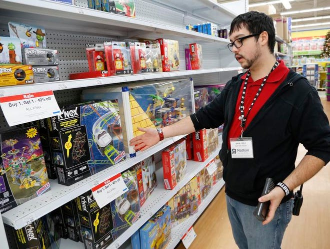 Nathan Pritchard points to a variety of K'Nex toys Dec. 13, 2013, at Toys R Us in Lafayette, Ind. Pritchard is a sales team member who specializes in electronics.