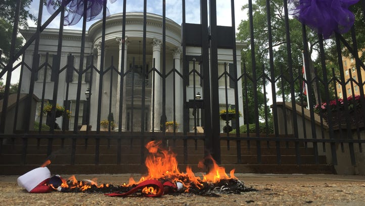 Activists burn a Mississippi state flag and a Confederate