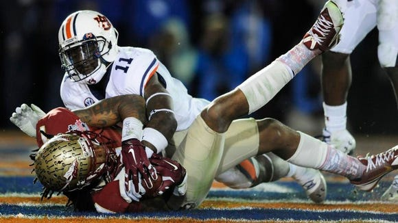 Jameis Winston threw the game-winning touchdown pass to receiver Kelvin Benjamin being defended by Chris Davis with 13 seconds left to beat Auburn, 34-31, in the national title game.