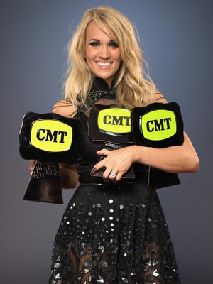 Singer Carrie Underwood poses for a portrait with three 2015 CMT Awards, for People.com during the 2015 CMT Music Awards at Bridgestone Arena on June 10, 2015 in Nashville, Tennessee.