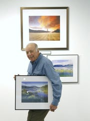 """Gary Thompson, one of the partners of Image City Photography Gallery, holds his photo """"Lake Everest."""""""