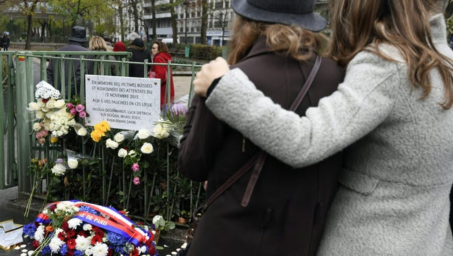 Two women stand in front of a wreath and a commemorative plaque in memory of the injured and killed victims of the Paris attacks after its unveiling on Nov. 13, 2016. France marked the first anniversary of the attacks that killed 130 on Nov. 13, 2015.