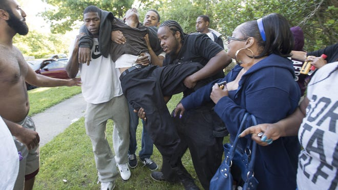 """A man who rushed toward the taped-off crime scene calls out, """"Where's my nephew? Where's my nephew?"""" before becoming faint and getting checked by medical personnel Monday morning at the scene of a triple fatal shooting on the 6500 block of Brace in Detroit."""