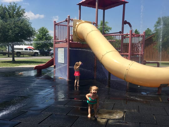 Sisters Avery and Marie Guidry enjoy a water playground at Poverty Point Reservoir State Park in Delhi.