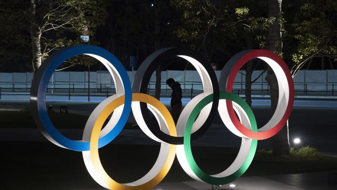 A man is seen through the Olympic rings in front of the New National Stadium in Tokyo on Tuesday.