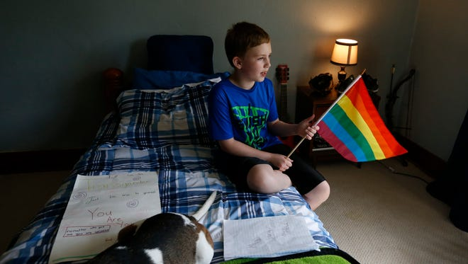 Bryan Brown, 10, holds a pride flag in his bedroom Tuesday, June 28, 2016, at his home in Orient, Iowa. Bryan, who was born a girl, wants to get a transgender pride flag to add to the rainbow flag he got at this year's Capital City Pride Festival.