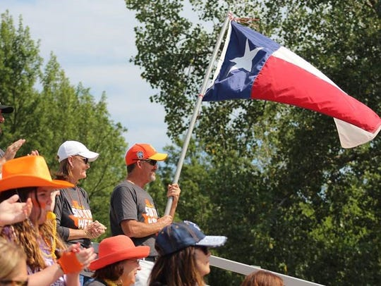 A fan holds the Texas flag during one of Wylie Little