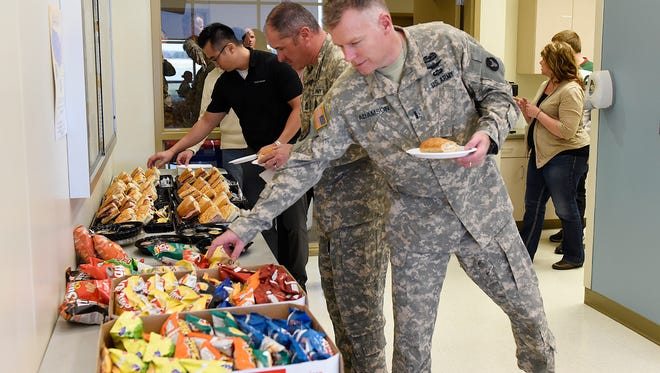 Minnesota National Guard Standardization Officer Paul Adamson grabs a sandwich and chips before sitting down with GeoComm Inc. employees for lunch Tuesday, Nov. 10 at the St. Cloud Army Aviation Facility. The appreciation event was scheduled in advance of Veterans Day.