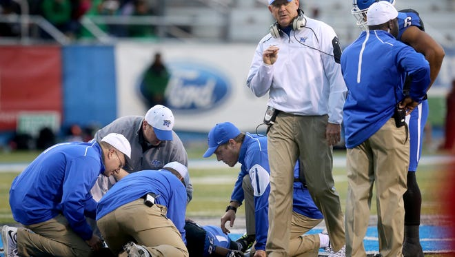 MTSU's head football coach Rick Stockstill goes onto the field to check on running back Desmond Anderson (25) after he was injured on a play against North Texas, during the NCAA college football game, on Saturday, Nov. 21, 2015, in Murfreesboro, Tenn. .
