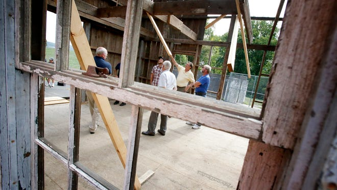 Friends of the Elmira Civil War Prison Camp and construction contractors marvel at the almost complete reconstruction of a prison camp building Friday.