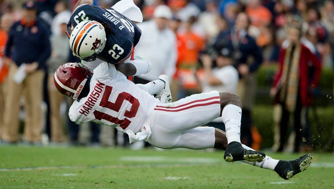 Alabama defensive back Ronnie Harrison tackles Auburn wide receiver Ryan Davis during their game Saturday.