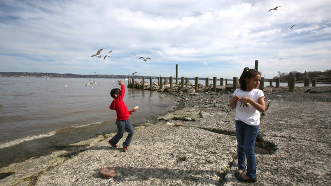 Larry Merice, 6, and Ghianna Smith, 7 both of Harrison, feed seagulls at Memorial Park in Nyack April 15, 2015. Behind them are piles for a pier which is being built to provide a viewing area for construction on the new Tappan Zee Bridge.