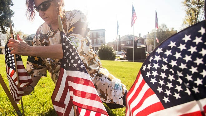 Terri Hinckley, of Loganville, places flags in honor of the fallen soldiers at the Prospect Hill Cemetery & Cremation Gardens Flag Re-Creation ceremony Saturday, April 16, 2016. Amanda J. Cain photo