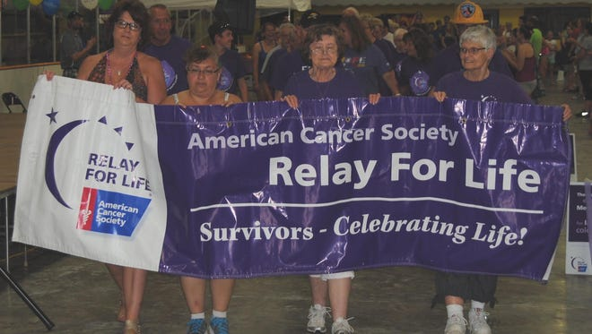 Cancer survivors walk the first lap around the track.